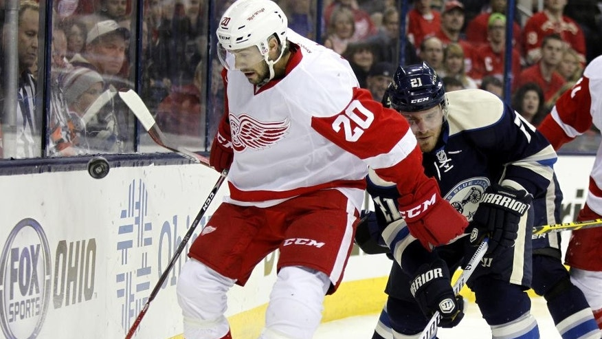 Detroit Red Wings' Drew Miller, left, works for the puck against Columbus Blue Jackets' James Wisniewski  in the first period of an NHL hockey game in Columbus, Ohio, Tuesday, March 25, 2014. (AP Photo/Paul Vernon)