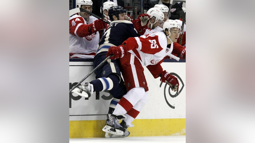 Detroit Red Wings' Danny DeKeyser, right, checks Columbus Blue Jackets' Brandon Dubinsky in the first period of an NHL hockey game in Columbus, Ohio, Tuesday, March 25, 2014. (AP Photo/Paul Vernon)