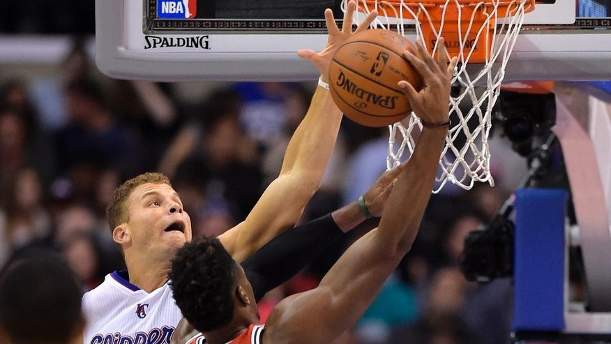 Los Angeles Clippers forward Blake Griffin, left, blocks the shot of Milwaukee Bucks forward Jeff Adrien during the first half of an NBA basketball game, Monday, March 24, 2014, in Los Angeles.  (AP Photo/Mark J. Terrill)