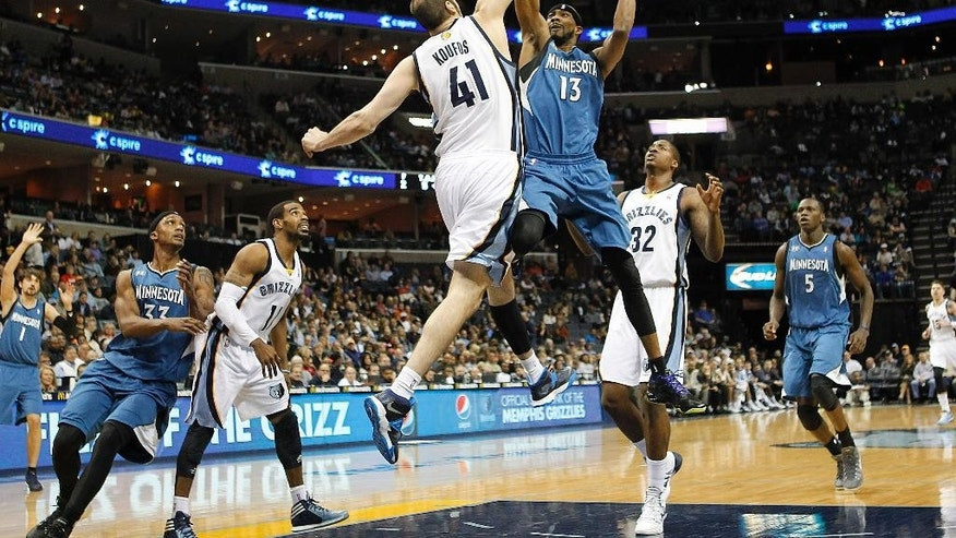 Minnesota Timberwolves forward Corey Brewer (13) goes to the basket against Memphis Grizzlies center Kosta Koufos (41) in the first half of an NBA basketball game Monday, March 24, 2014, in Memphis, Tenn. (AP Photo/Lance Murphey)