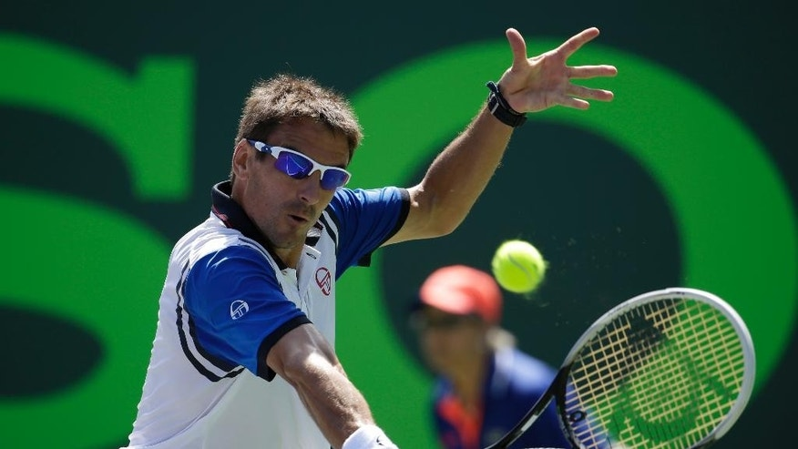 Tommy Robredo, of Spain, returns to Novak Djokovic at the Sony Open Tennis tournament, Tuesday, March 25, 2014, in Key Biscayne, Fla. (AP Photo/Lynne Sladky)