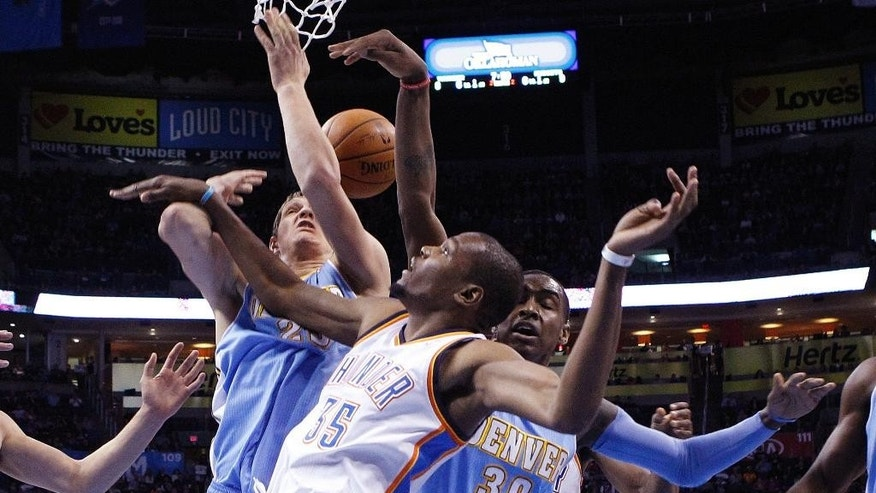 Oklahoma City Thunder forward Kevin Durant (35) loses the ball under the basket in front of Denver Nuggets center Timofey Mozqov (25) and forward Quincy Miller (30) in the first quarter of an NBA basketball game in Oklahoma City, Monday, March 24, 2014. (AP Photo/Sue Ogrocki)