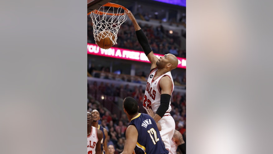 Chicago Bulls forward Taj Gibson (22) dunks over Indiana Pacers forward Evan Turner during the first half of an NBA basketball game Monday, March 24, 2014, in Chicago. (AP Photo/Charles Rex Arbogast)