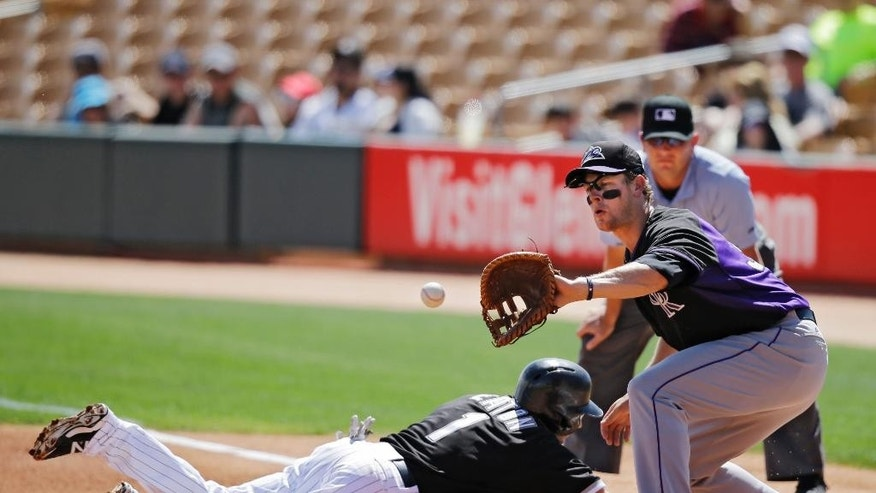 Chicago White Sox's Adam Eaton (1) dives safely back into first as Colorado Rockies first baseman Justin Morneau waits for the pickoff throw in the first inning of a spring exhibition baseball game Tuesday, March 25, 2014, in Glendale, Ariz. (AP Photo/Mark Duncan)