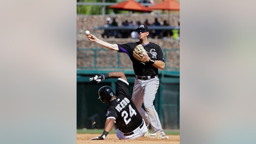 Colorado Rockies second baseman DJ LeMahieu throws over Chicago White Sox's Dayan Viciedo (24) to complete a double play on Alexei Ramirez in the fifth inning of a spring exhibition baseball game Tuesday, March 25, 2014, in Glendale, Ariz. (AP Photo/Mark Duncan)