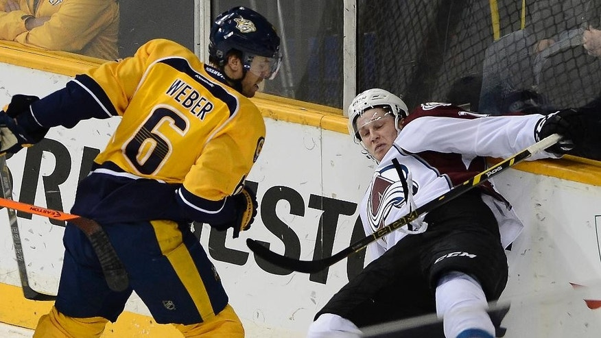 Nashville Predators defenseman Shea Weber (6) checks Colorado Avalanche center Nathan MacKinnon (29) into the boards in the second period of an NHL hockey game on Tuesday, March 25, 2014, in Nashville, Tenn. (AP Photo/Mark Zaleski)