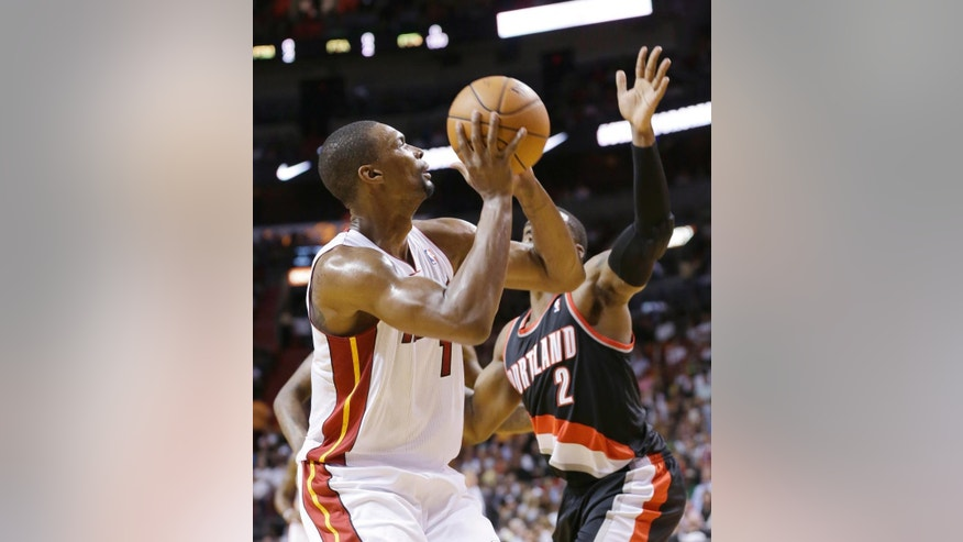 Miami Heat center Chris Bosh (1) goes up for a shot against Portland Trail Blazers guard Wesley Matthews (2) during the first half of an NBA basketball game, Monday, March 24, 2014 in Miami. Bosh finished with 15 points as the Heat defeated the Trail Blazers 93-91. (AP Photo/Wilfredo Lee)