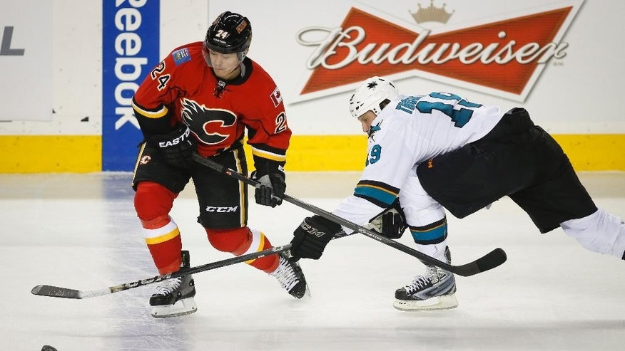 San Jose Sharks' Joe Thornton, right, stick checks Calgary Flames' Jiri Hudler, from the Czech Republic, during second period NHL hockey action in Calgary, Monday, March 24, 2014.  (AP Photo/The Canadian Press, Jeff McIntosh)