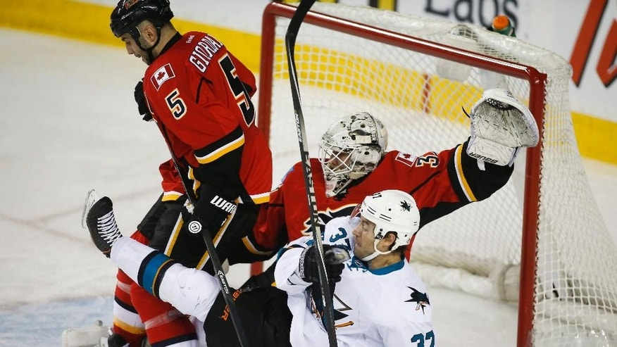 San Jose Sharks' Adam Burish, right, gets knocked to the ice by Calgary Flames' Mark Giordano, left, as goalie Karri Ramo, from Finland, guards the net during second period NHL hockey action in Calgary, Monday, March 24, 2014. (AP Photo/The Canadian Press, Jeff McIntosh)