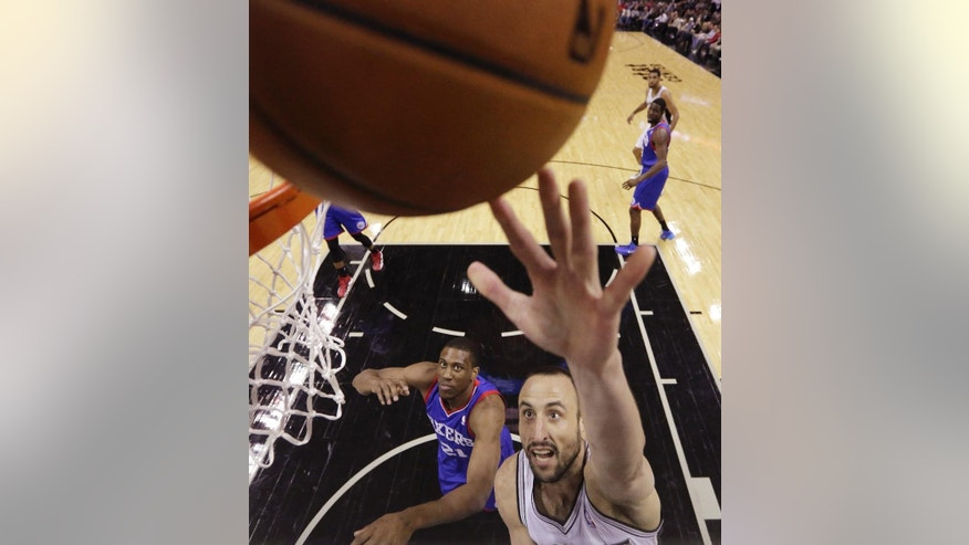 San Antonio Spurs' Manu Ginobili (20), of Argentina, scores as 76ers' Thaddeus Young (21) looks on during the first half of an NBA basketball game, Monday, March 24, 2014, in San Antonio. (AP Photo/Eric Gay)