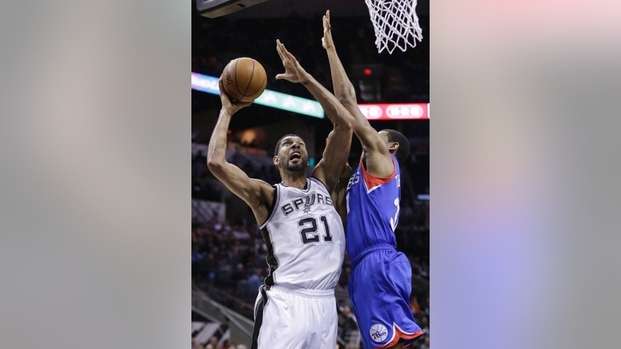 San Antonio Spurs' Tim Duncan (21) shoots over 76ers' Hollis Thompson, right, during the first half of an NBA basketball game, Monday, March 24, 2014, in San Antonio. (AP Photo/Eric Gay)