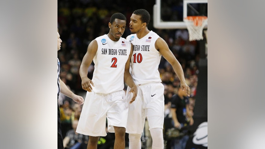 San Diego State's Xavier Thames (2) and Aqeel Quinn (10) react after a basket by teammate Xavier Thames in the first half during the third-round game of the NCAA men's college basketball tournament against North Dakota State in Spokane, Wash., Saturday, March 22, 2014. (AP Photo/Young Kwak)