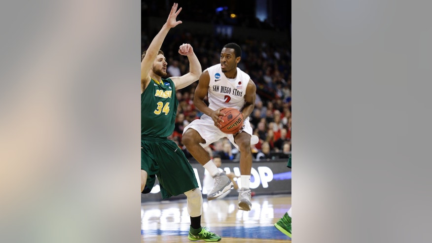San Diego State's Xavier Thames (2) tries to drive the lane in front of North Dakota State's Chris Kading in the first half during the third-round of the NCAA men's college basketball tournament in Spokane, Wash., Saturday, March 22, 2014. (AP Photo/Elaine Thompson)