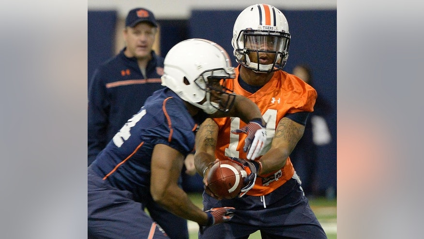 In this photo taken on Tuesday, March 18, 2014, Auburn quarterback Nick Marshall (14) hands off to running back Cameron Artis-Payne (44) during Auburn's first spring NCAA college football practice at the Auburn Athletic Complex in Auburn, Ala. (AP PHOTO/AL.com, Julie Bennett) MAGS OUT