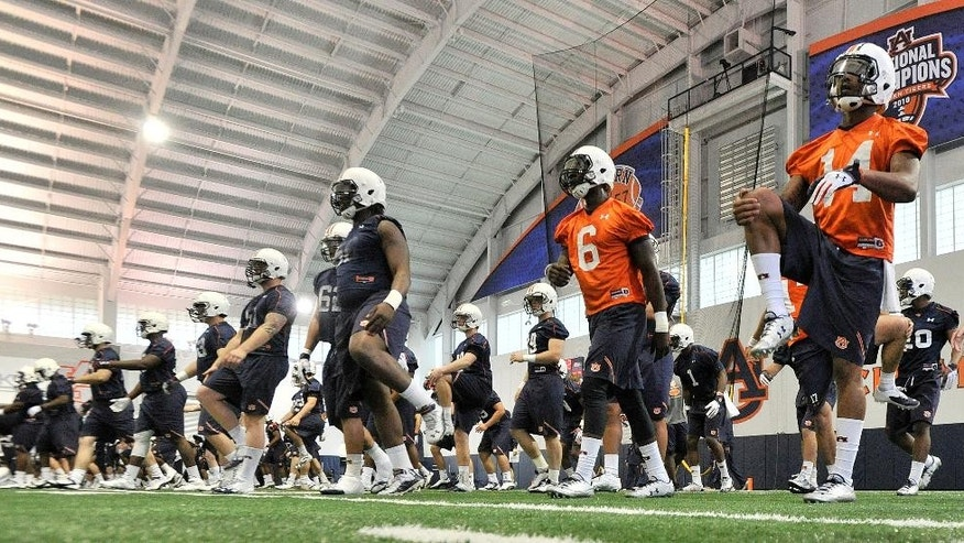 In this photo taken on Tuesday, March 18, 2014, Auburn quarterbacks Jeremy Johnson (6) and Nick Marshall (14) stretch during Auburn's first spring NCAA college football practice at the Auburn Athletic Complex in Auburn, Ala. (AP PHOTO/AL.com, Julie Bennett) MAGS OUT