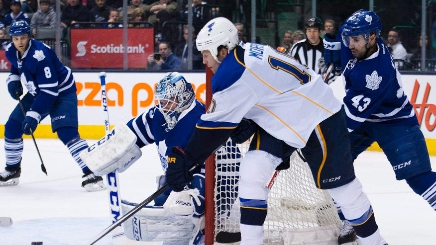 Toronto Maple Leafs goalie Jonathan Bernier, hugs the goal post as St. Louis Blues forward Brenden Morrow, second right, tries for the wrap around past Maple Leafs forward Nazem Kadri during third period NHL hockey action in Toronto on Tuesday, March 25, 2014. (AP Photo/The Canadian Press, Nathan Denette)