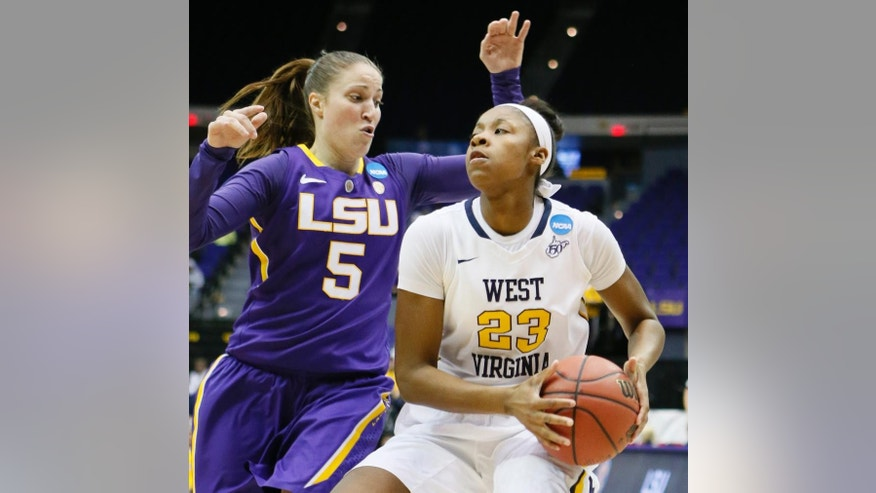 West Virginia guard Bria Holmes (23) looks for an opening to the goal as LSU guard Jeanne Kenney (5) defends in the first half of an NCAA college basketball second-round tournament game Tuesday, March 25, 2014, in Baton Rouge, La. (AP Photo/Rogelio V. Solis)