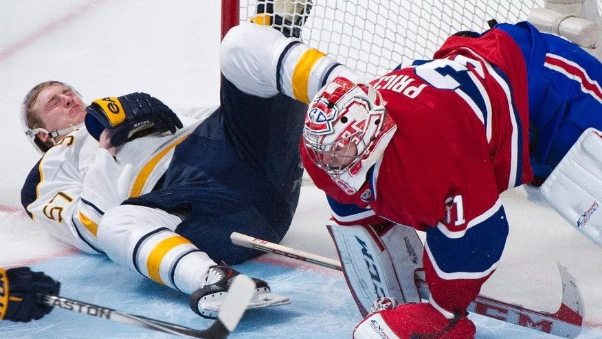 Buffalo Sabres' Tyler Myers collides with Montreal Canadiens goaltender Carey Price during the third period of an NHL hockey game Tuesday, March 25, 2014, in Montreal. Montreal won 2-0. (AP Photo/The Canadian Press, Graham Hughes)