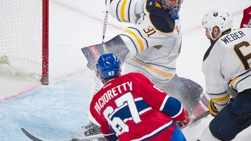Montreal Canadiens' Max Pacioretty scores against Buffalo Sabres goaltender Matt Hackett as Sabres' Mike Weber during the third period of an NHL hockey game Tuesday, March 25, 2014, in Montreal. (AP Photo/The Canadian Press, Graham Hughes)