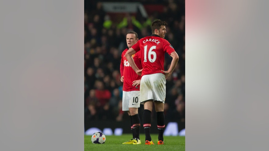 Manchester United's Wayne Rooney, left, and Michael Carrick wait for play to begin after a second goal by Manchester City's Edin Dzeko, out of frame. during their English Premier League soccer match at Old Trafford Stadium, Manchester, England, Tuesday March 25, 2014. (AP Photo/Jon Super)