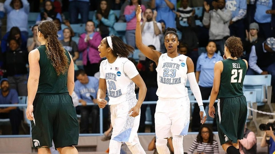 North Carolina's Diamond DeShields (23) and teammate Danielle Butts (10), along with Michigan State's Tori Jankoska, left, and Klarissa Bell (21) walk the court during following the teams' second-round game of the NCAA college basketball tournament in Chapel Hill, N.C. Tuesday, March 25, 2014. North Carolina beat Michigan State 62-53. (AP Photo/Ellen Ozier)