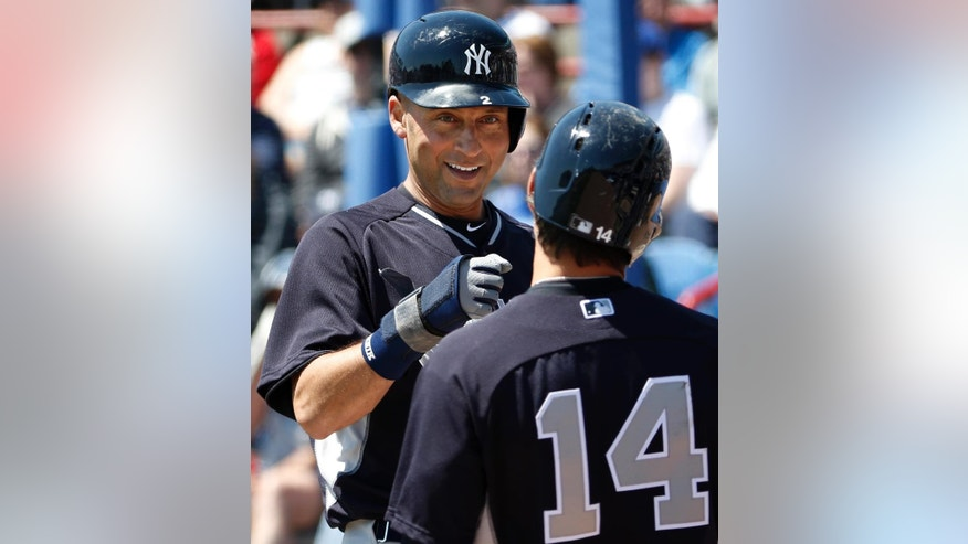 New York Yankees' Derek Jeter greets Brian Roberts after scoring on Kelly Johnson's first-inning, two-run single in a spring training baseball game against the Toronto Blue Jays in Dunedin, Fla., Wednesday, March 26, 2014. The Blue Jays defeated the Yankees 10-6. (AP Photo/Kathy Willens)