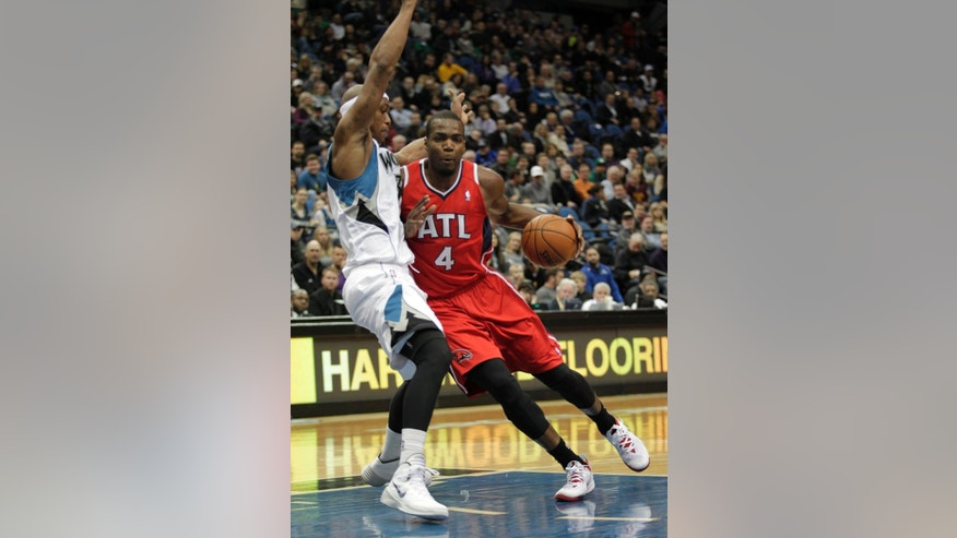 Atlanta Hawks forward Paul Millsap (4) drives against Minnesota Timberwolves forward Dante Cunningham (33) during the first half of an NBA basketball game, Wednesday, March 26, 2014, in Minneapolis. (AP Photo/Paul Battaglia)