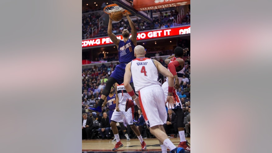 Phoenix Suns' Markieff Morris (11) dunks while Washington Wizards' Marcin Gortat (4) watches during the first half of an NBA basketball game in Washington, Wednesday, March 26, 2014. (AP Photo/Manuel Balce Ceneta)