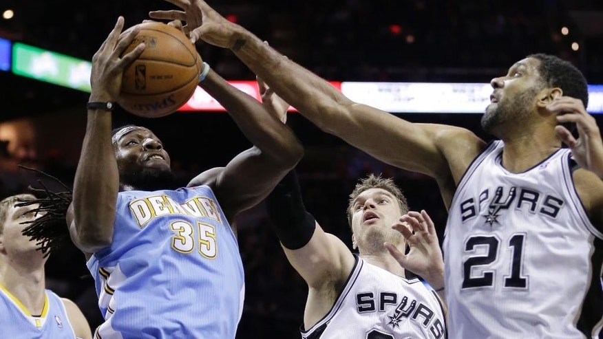 Denver Nuggets' Kenneth Faried (35) grabs a rebound against San Antonio Spurs'  Tiago Splitter (22) and Tim Duncan (21) for a rebound during the first half of an NBA basketball game, Wednesday, March 26, 2014, in San Antonio. (AP Photo/Eric Gay)