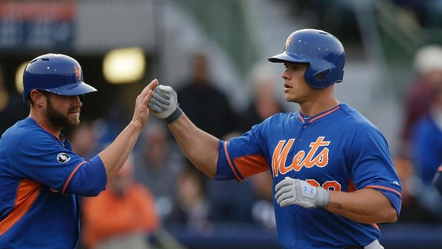 New York Mets' Anthony Recker, right, is congratulated by teammate Andrew Brown after they both scored on Recker's two-run home run in the fifth inning of a spring exhibition baseball game against the Houston Astros in Kissimmee, Fla., Wednesday, March 26, 2014. (AP Photo/Carlos Osorio)