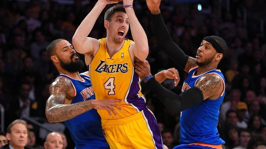 Los Angeles Lakers forward Ryan Kelly, center, tries to pass the ball under pressure from New York Knicks center Tyson Chandler, left, and forward Carmelo Anthony during the first half of an NBA basketball game, Tuesday, March 25, 2014, in Los Angeles. (AP Photo/Mark J. Terrill)