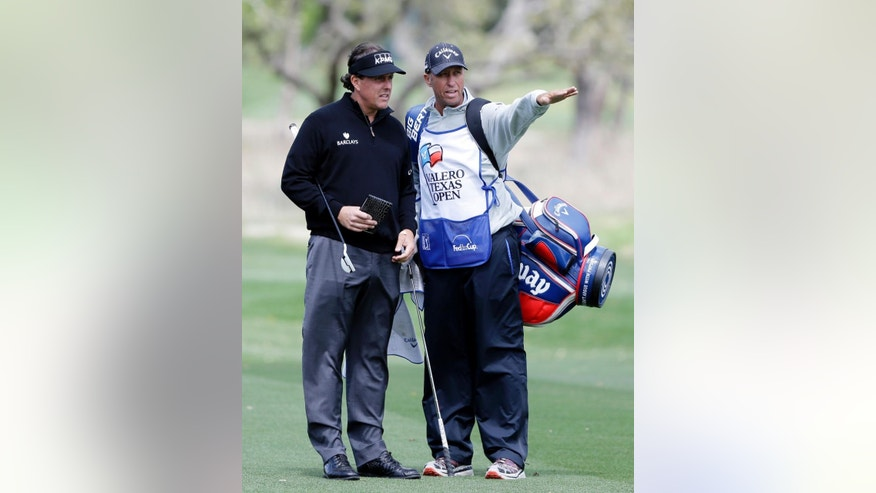 Phil Mickelson, left, gets direction from his caddie as he takes part in a pro-am at the Valero Texas Open, Wednesday, March 26, 2014, in San Antonio. Mickelson is straying from his usual schedule and playing in the Valero Texas Open for the first time in 22 years. (AP Photo/Eric Gay)