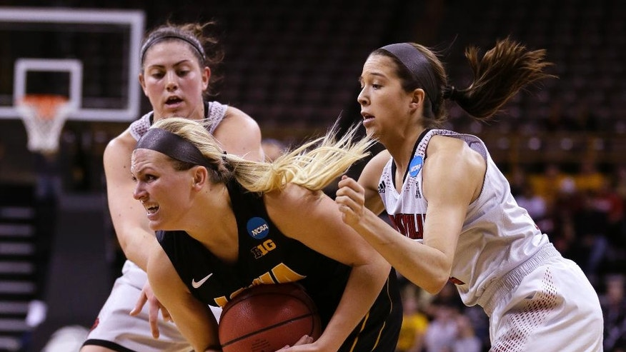 Iowa guard Melissa Dixon, center, looks to pass between Louisville's Sara Hammond, left, and Jude Schimmel, right, during the first half of an NCAA tournament second-round women's college basketball game, Tuesday, March 25, 2014, in Iowa City, Iowa. (AP Photo/Charlie Neibergall)