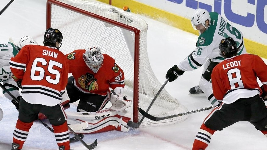Dallas Stars left wing Ryan Garbutt (16) scores past the toe of Chicago Blackhawks goalie Corey Crawford (50) as Andrew Shaw (65) and Nick Leddy (8) watch during the third period of an NHL hockey game Tuesday, March 25, 2014, in Chicago. The Blackhawks won 4-2. (AP Photo/Charles Rex Arbogast)
