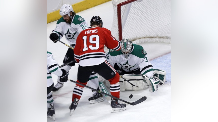 Dallas Stars goalie Kari Lehtonen (32) makes a save on a shot by Chicago Blackhawks center Jonathan Toews (19) as Jordie Benn (24) also defends during the first period of an NHL hockey game Tuesday, March 25, 2014, in Chicago. (AP Photo/Charles Rex Arbogast)