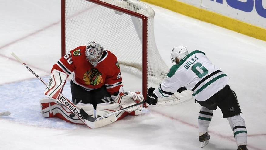 Chicago Blackhawks goalie Corey Crawford (50) makes a save on a shot by Dallas Stars defenseman Trevor Daley (6) during the third period of an NHL hockey game Tuesday, March 25, 2014, in Chicago. The Blackhawks won 4-2. (AP Photo/Charles Rex Arbogast)