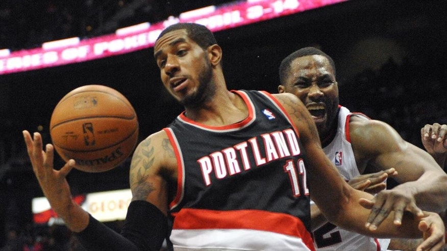 Portland Trail Blazers' LaMarcus Aldridge (12) brings down the rebound in front of Atlanta Hawks' Elton Brand, right, in the first half of their NBA basketball game Thursday, March 27, 2014, in Atlanta. (AP Photo/David Tulis)