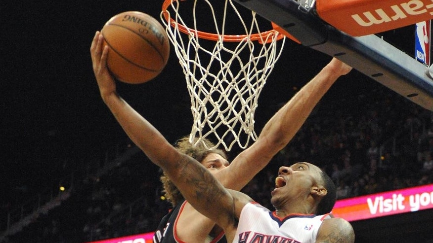 Atlanta Hawks' Jeff Teague (0) shoots the layup around Portland Trail Blazers' Robin Lopez (42) in the first half of their NBA basketball game Thursday, March 27, 2014, in Atlanta. (AP Photo/David Tulis)