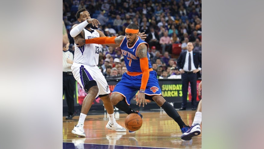 New York Knicks forward Carmelo Anthony, right, drives to the basket against Sacramento Kings defender Derrick Williams during the first half of an NBA basketball game in Sacramento, Calif., Wednesday, March 26, 2014. (AP Photo/Steve Yeater)