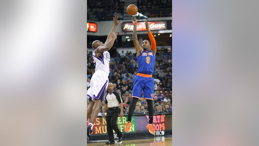 New York Knicks guard J.R. Smith (8) shoots over Sacramento Kings defender Travis Outlaw (25) during the first half of an NBA basketball game in Sacramento, Calif., on Wednesday, March 26, 2014.(AP Photo/Steve Yeater)