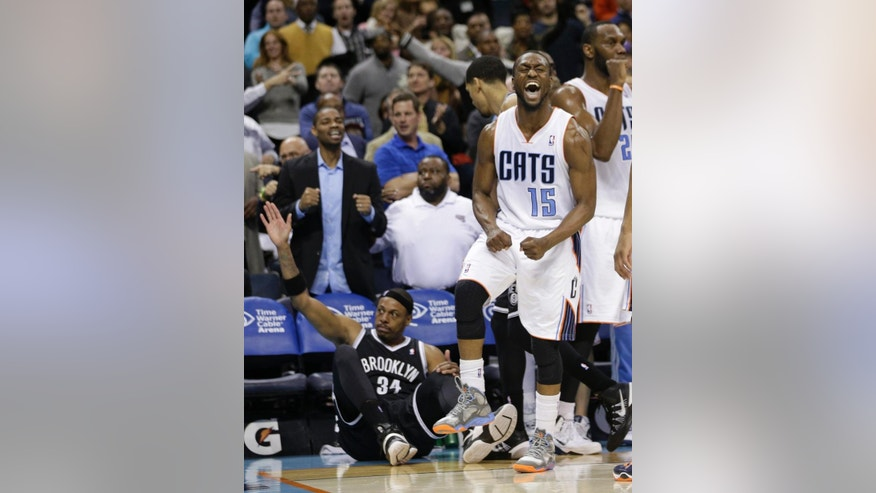 Charlotte Bobcats' Kemba Walker (15) celebrates after Brooklyn Nets' Paul Pierce (34) knocked the ball out of bounds during overtime of an NBA basketball game in Charlotte, N.C., Wednesday, March 26, 2014. The Bobcats won 116-111. (AP Photo/Chuck Burton)