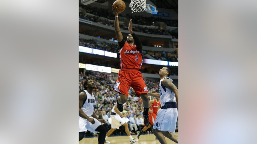 Los Angeles Clippers guard Chris Paul (3) drives to the basket between Dallas Mavericks defenders Jae Crowder, left, and Devin Harris, right, during the first half of an NBA basketball game Thursday, March 27, 2014, in Dallas. (AP Photo/LM Otero)