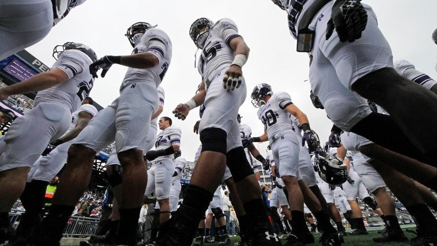 FILE - In this Saturday, Oct 6, 2012, file photo, the Northwestern football team heads to the locker room after warming up before an NCAA college football game against Penn State in State College, Pa. A ruling Wednesday, March 26, 2014, that the Northwestern football team can bargain with the school as employees represented by a union may not by itself change the way amateur sports operate. But it figures to put more pressure on the NCAA and the major conferences to give something back to the players to justify the billions of dollars the players bring in _ and never see. (AP Photo/Gene J. Puskar, File)