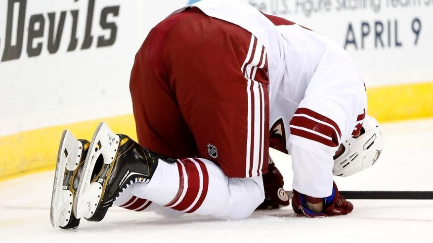Phoenix Coyotes right wing David Moss is slow off the ice after hitting the board while competing for the puck with New Jersey Devils' Eric Gelinas during the first period of an NHL hockey game, Thursday, March 27, 2014, in Newark, N.J. (AP Photo/Julio Cortez)