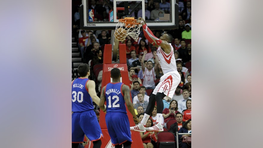 Houston Rockets' Dwight Howard, right, dunks over Philadelphia 76ers' James Nunnally (12) and Byron Mullens (30) during the first half of an NBA basketball game on Thursday, March 27, 2014, in Houston. (AP Photo/Bob Levey)