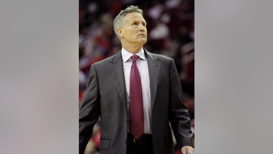Philadelphia 76ers head coach Brett Brown checks the scoreboard during the first half of an NBA basketball game against the Houston Rockets, Thursday, March 27, 2014, in Houston. (AP Photo/Bob Levey)
