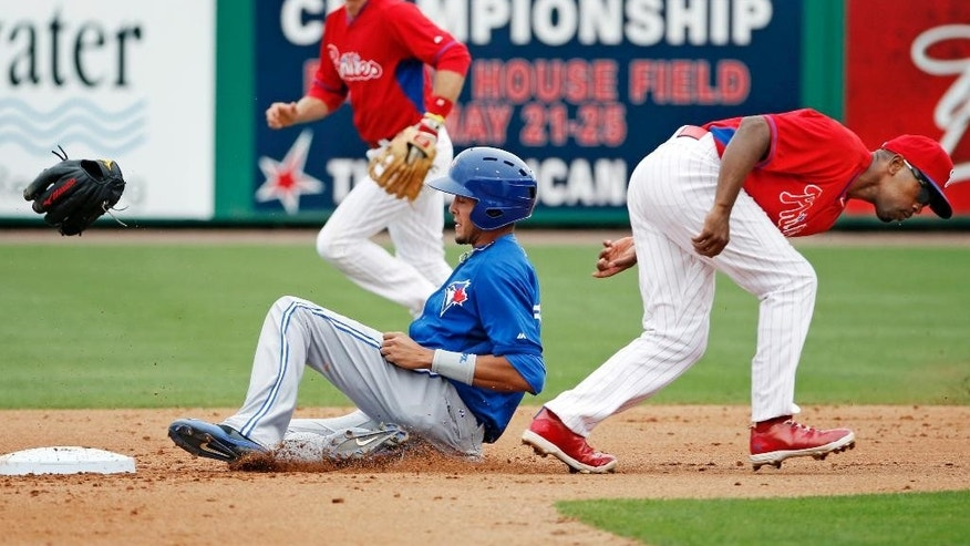 Philadelphia Phillies second baseman Chase Utley, left, watches as shortstop Jimmy Rollins, right, loses his glove trying to tag out Toronto Blue Jays pinch runner Emilio Guerrero on a fourth-inning stolen base in a spring exhibition baseball game in Clearwater, Fla., Thursday, March 27, 2014. (AP Photo/Kathy Willens)