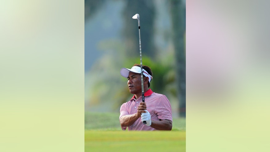 Thailand's Thongchai Jaidee watches his shot from the rough on the first hole during the first round of the Eurasia Cup golf tournament at the Glenmarie Golf and Country Club in Subang, Malaysia, Thursday, March 27, 2014. (AP Photo/Joshua Paul)
