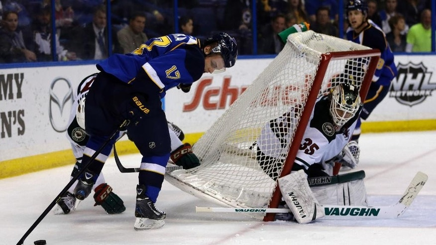 Minnesota Wild goalie Darcy Kuemper, right, keeps his eye on the puck after the net was moved by St. Louis Blues' Vladimir Sobotka, of the Czech Republic, while chasing after a loose puck during the second period of an NHL hockey game Thursday, March 27, 2014, in St. Louis. (AP Photo/Jeff Roberson