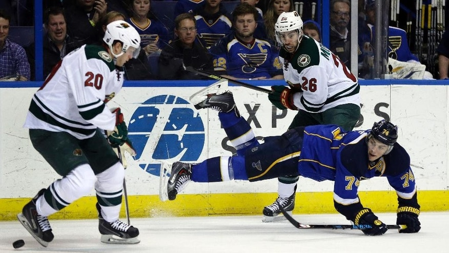 St. Louis Blues' T.J. Oshie (74) pass around Minnesota Wild's Ryan Suter (20) after falling over the stick of Minnesota Wild's Matt Moulson (26) during the second period of an NHL hockey game Thursday, March 27, 2014, in St. Louis. (AP Photo/Jeff Roberson)